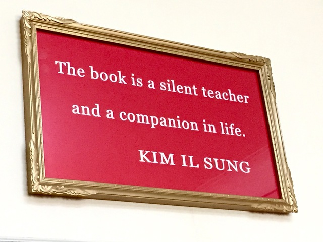 "[Photo of a framed sign reading, ""The book is a silent teacher and a companion in life. —Kim Il Sung""]"
