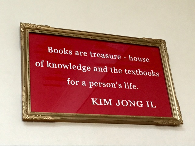 "[Photo of a sign reading, ""Books are treasure-house of knowledge and the textbooks for a person""s life. —Kim Jong Il""]"